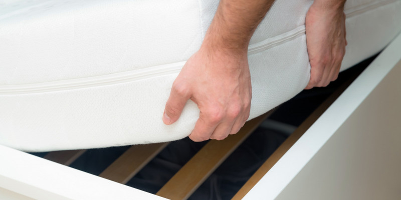 man-hands-lifting-the-mattress-at-the-bedroom-looking-at-the-bed-frame.jpg